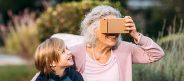 Grandmother using cardboard with grandchild